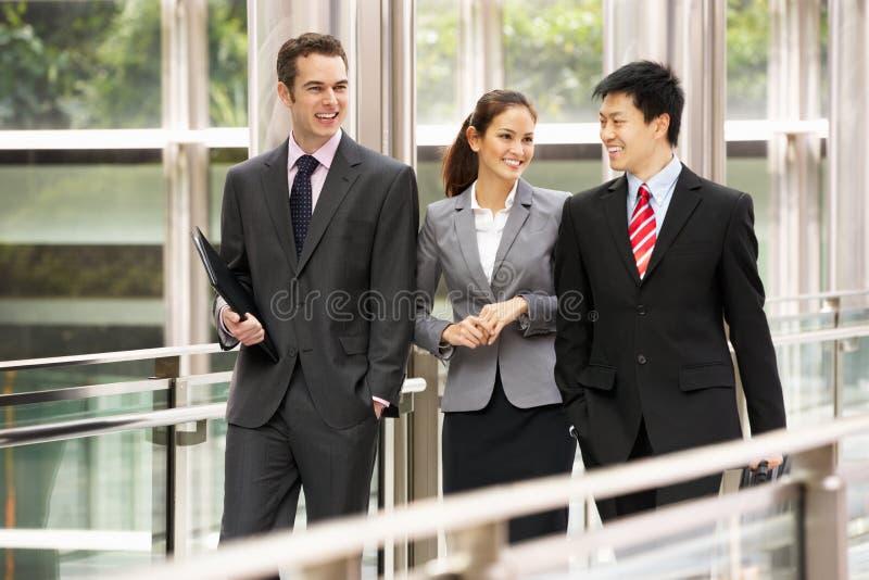 Τρεις επιχειρησιακοί συνάδελφοι που κουβεντιάζουν το περπάτημα στοκ εικόνα