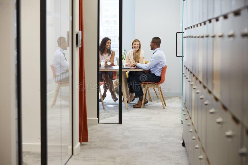 Τρεις επιχειρησιακοί συνάδελφοι σε μια άτυπη συνεδρίαση των γραφείων στοκ φωτογραφίες