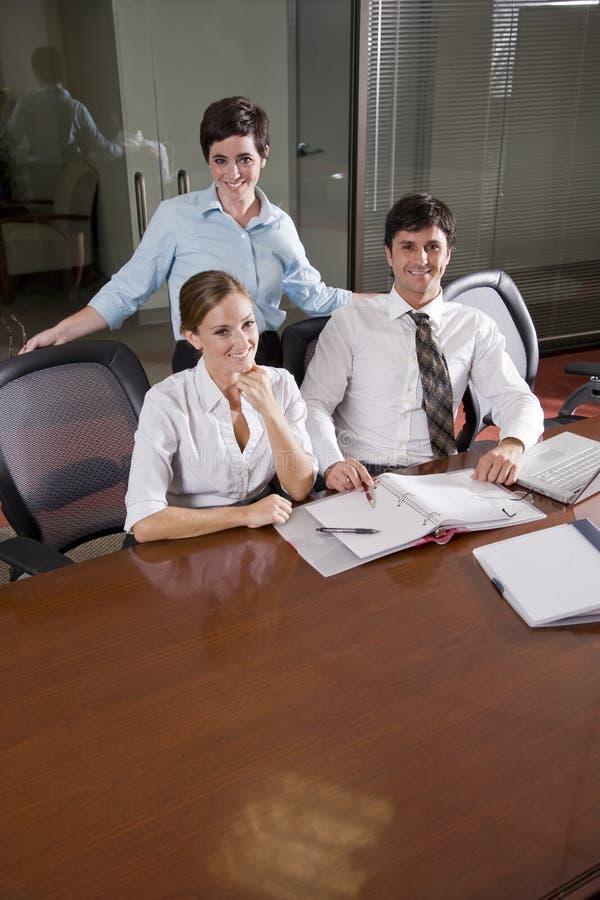Τρεις εργαζόμενοι γραφείων που εργάζονται στην αίθουσα συνεδριάσεων στοκ εικόνα με δικαίωμα ελεύθερης χρήσης