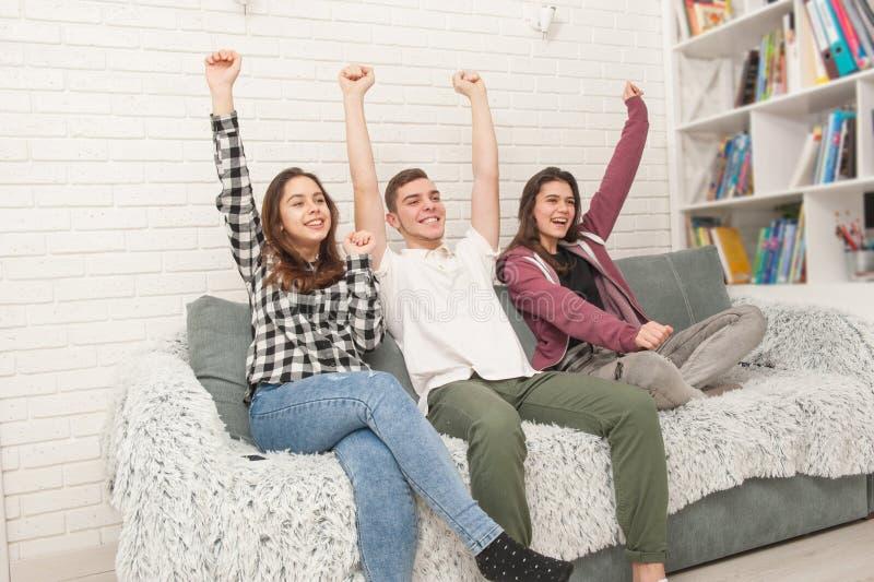 Τρεις εφηβικοί θαυμαστές κάθονται στον καναπέ και τη TV προσοχής στοκ φωτογραφία με δικαίωμα ελεύθερης χρήσης