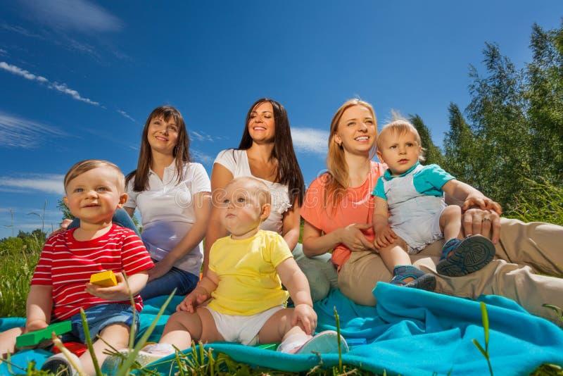Τρεις εύθυμες μητέρες με τα μωρά τους στη χλόη στοκ φωτογραφίες