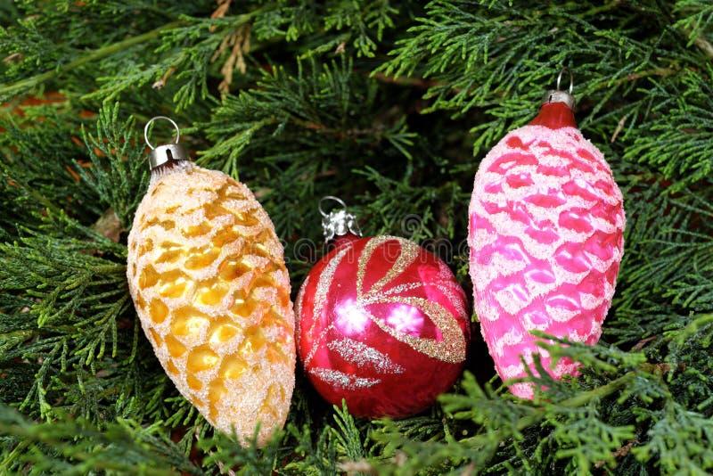 Τρεις ζωηρόχρωμες διακοσμήσεις Χριστουγέννων στις πράσινες βελόνες πεύκων στοκ φωτογραφίες