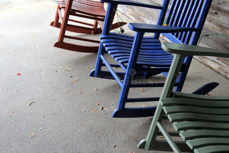 Τρεις ζωηρόχρωμες λικνίζοντας καρέκλες στο τσιμέντο στοκ εικόνες