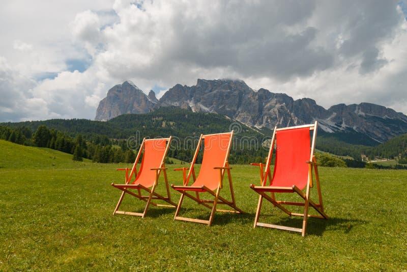 Τρεις ζωηρόχρωμες καρέκλες γεφυρών μπροστά από το όμορφο βουνό Tofane στοκ εικόνα