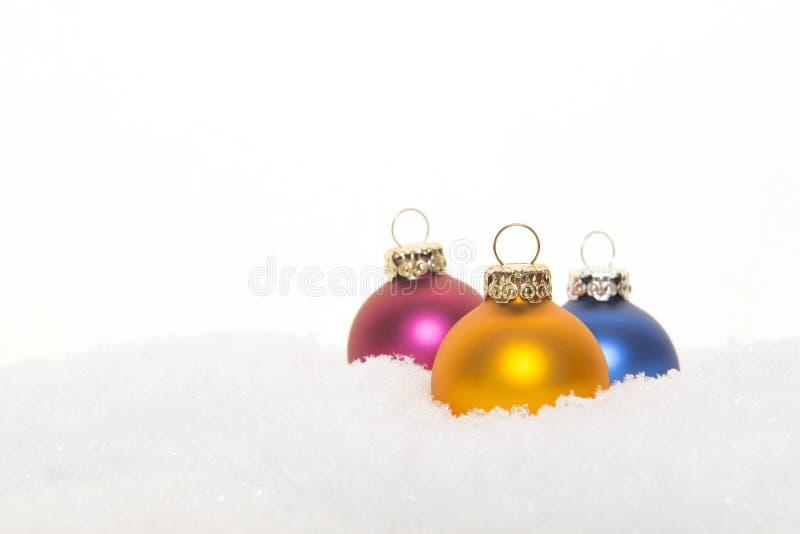 Τρεις ζωηρόχρωμες σφαίρες διακοσμήσεων Χριστουγέννων στο χιόνι σε μια λευκιά ΤΣΕ στοκ εικόνες