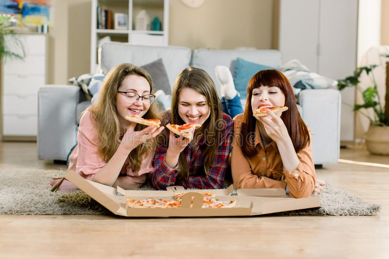 Τρεις θηλυκοί φίλοι που τρώνε την πίτσα στο κόμμα σπιτιών στο πάτωμα στο άνετο δωμάτιο στοκ φωτογραφία με δικαίωμα ελεύθερης χρήσης