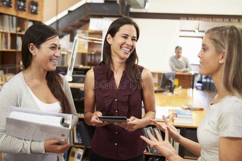 Τρεις θηλυκοί αρχιτέκτονες που κουβεντιάζουν στο σύγχρονο γραφείο από κοινού στοκ φωτογραφία με δικαίωμα ελεύθερης χρήσης