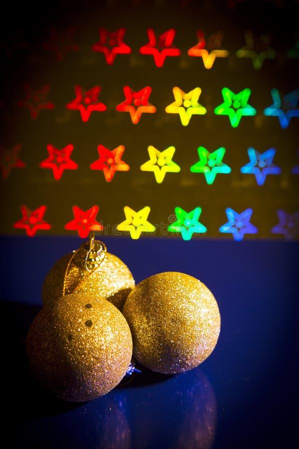 Τρεις κίτρινες σφαίρες Χριστουγέννων στο υπόβαθρο αστεριών του φωτεινού χρώματος στοκ εικόνα