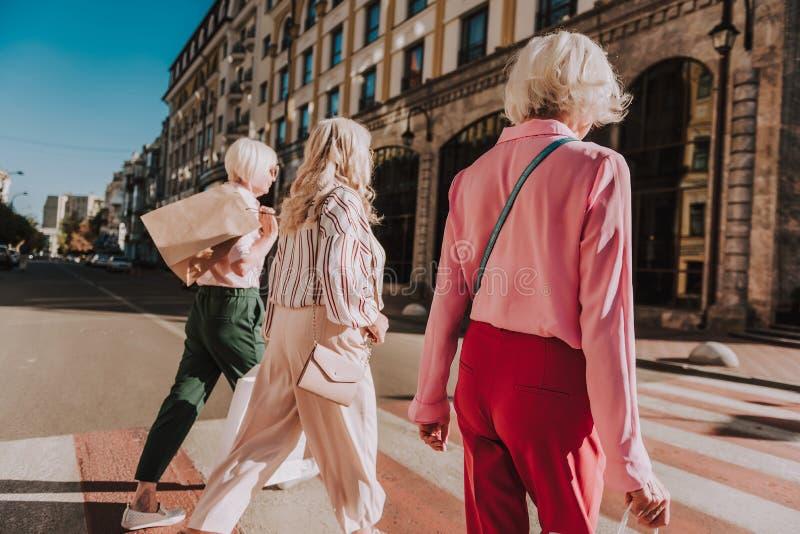 Τρεις καθιερώνουσες τη μόδα ενήλικες γυναίκες ξοδεύουν το χρόνο από κοινού στοκ εικόνα
