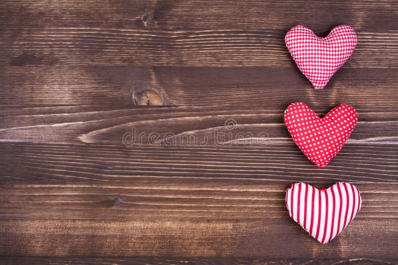 Τρεις καρδιές στο ξύλινο υπόβαθρο στοκ φωτογραφία