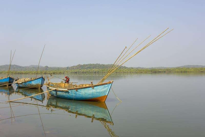 Τρεις κενές βάρκες με την αλιεία των ράβδων και των μηχανών στο νερό ενάντια στο σκηνικό του ποταμού στοκ εικόνες