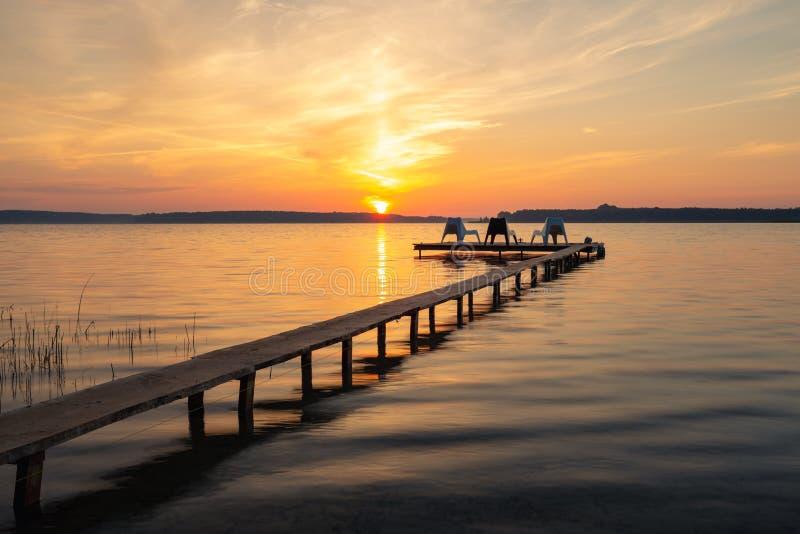 Τρεις κενές καρέκλες στον ξύλινο λιμενοβραχίονα στη λίμνη στοκ εικόνες