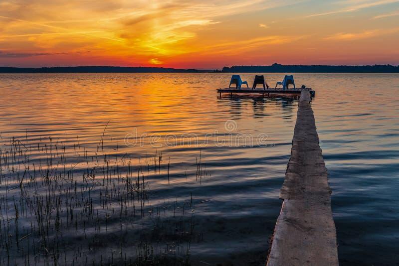 Τρεις κενές καρέκλες στον ξύλινο λιμενοβραχίονα στη λίμνη στοκ φωτογραφία
