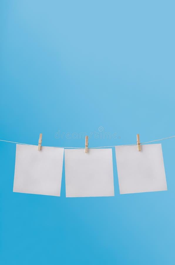 Τρεις κενές σημειώσεις που στερεώνονται στη γραμμή πλύσης στο μπλε ουρανό στοκ εικόνες