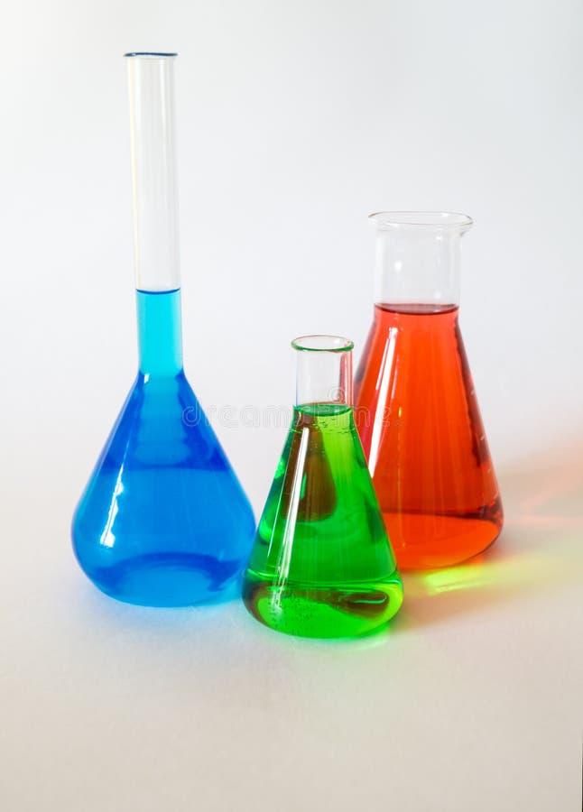 Τρεις κούπες γυαλιού που γεμίζουν με το χρωματισμένο υγρό στοκ εικόνες