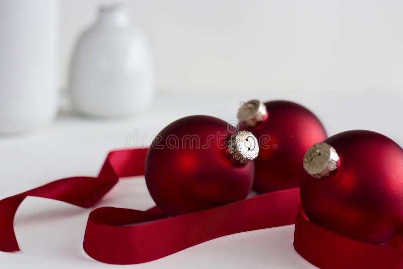 Τρεις κόκκινες διακοσμήσεις Χριστουγέννων με την κορδέλλα στοκ εικόνες