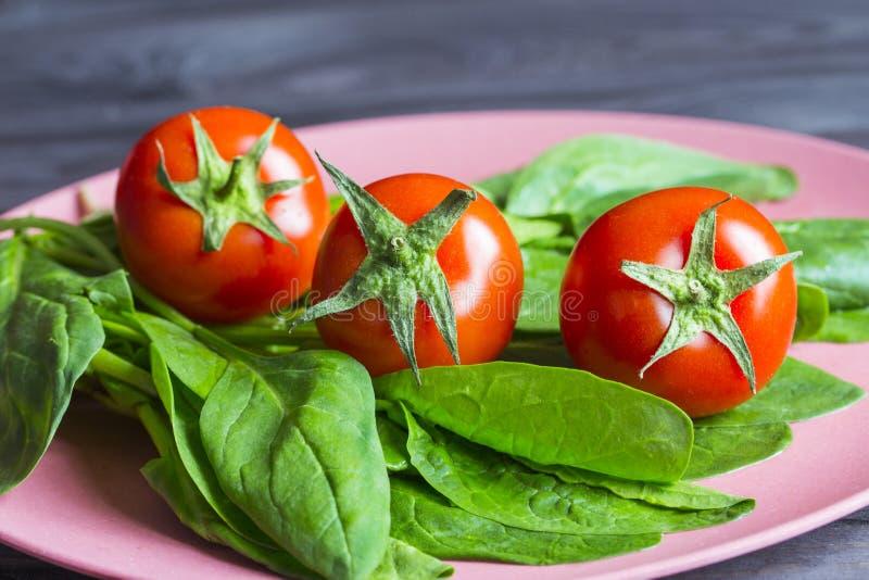 Τρεις κόκκινες ντομάτες κερασιών και πράσινα φύλλα σπανακιού σε ένα πιάτο μπαμπού Φρέσκα αγροτικά λαχανικά, υγιή τρόφιμα βιταμινώ στοκ εικόνες