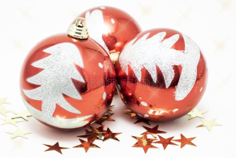 Τρεις κόκκινες σφαίρες που διακοσμούνται με ένα ασήμι ακτινοβολούν δέντρο για τα Χριστούγεννα μαζί με τα χρυσά αστέρια στοκ φωτογραφία με δικαίωμα ελεύθερης χρήσης