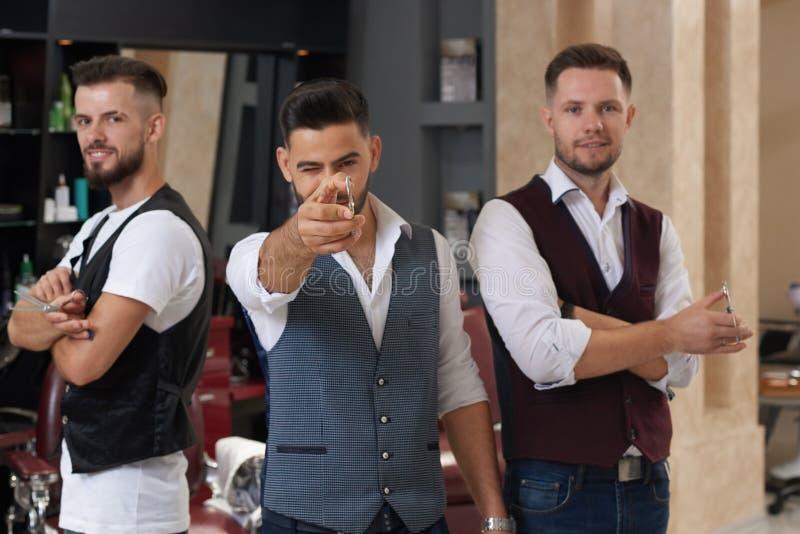 Τρεις κύριοι που θέτουν με το ψαλίδι στο barbershop στοκ εικόνες