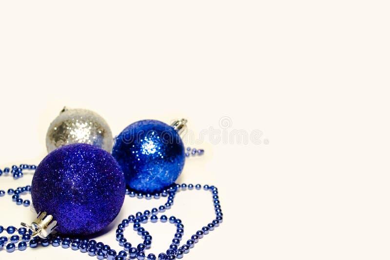 Τρεις λαμπρές σφαίρες Χριστουγέννων με τις χάντρες στο άσπρο υπόβαθρο στο αριστερό στοκ φωτογραφία