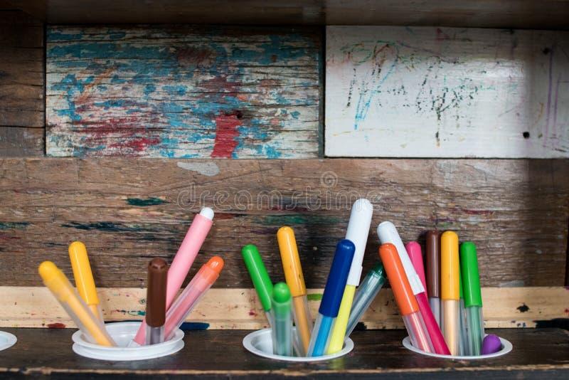 Τρεις μάνδρες δεικτών με τα διαφορετικά χρώματα σε ένα ξύλινο ράφι με το ρ στοκ εικόνα