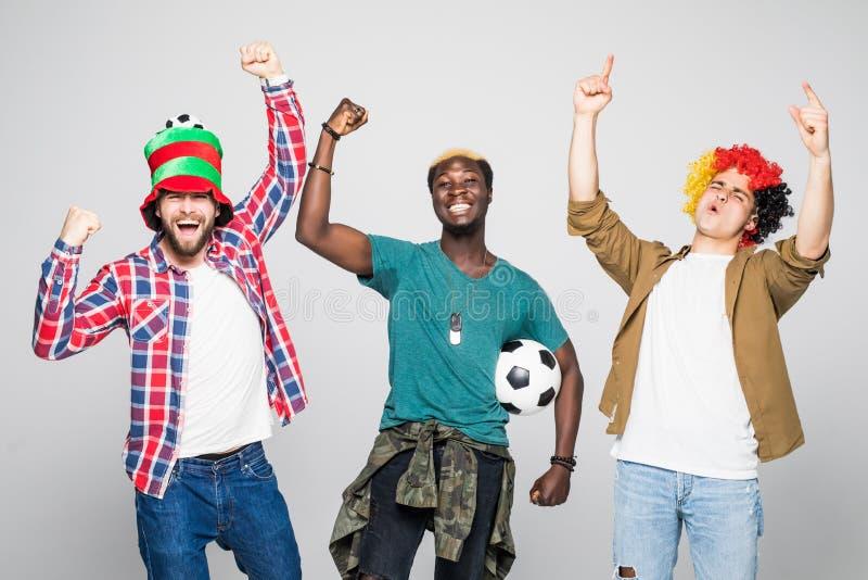 Τρεις μικτοί θαυμαστές φυλών των αθλητικών ομάδων γιορτάζουν τη νίκη και υποστηρίζουν τις ομάδες τους που απομονώνονται στο άσπρο στοκ φωτογραφίες