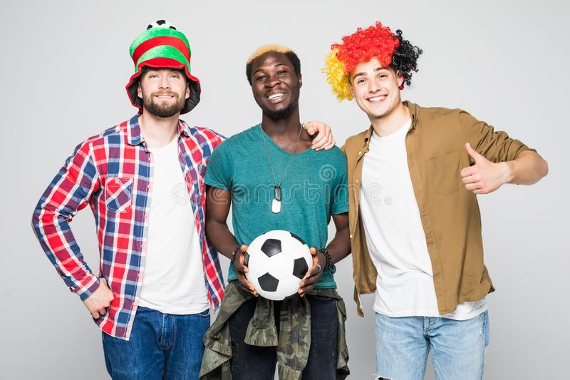 Τρεις μικτοί θαυμαστές φυλών των αθλητικών ομάδων γιορτάζουν τη νίκη και υποστηρίζουν τις ομάδες τους που απομονώνονται στο άσπρο στοκ εικόνα