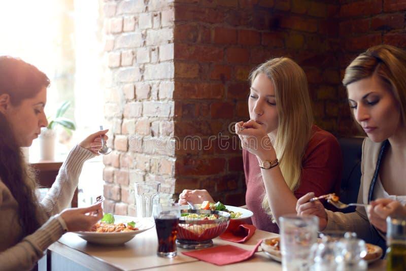 Τρεις νέες γυναίκες που χαλαρώνουν πέρα από το μεσημεριανό γεύμα στοκ φωτογραφία με δικαίωμα ελεύθερης χρήσης