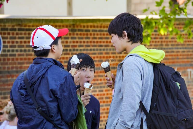 Τρεις νέοι ασιατικοί τουρίστες που τρώνε τους κώνους παγωτού στο South Bank στοκ φωτογραφία