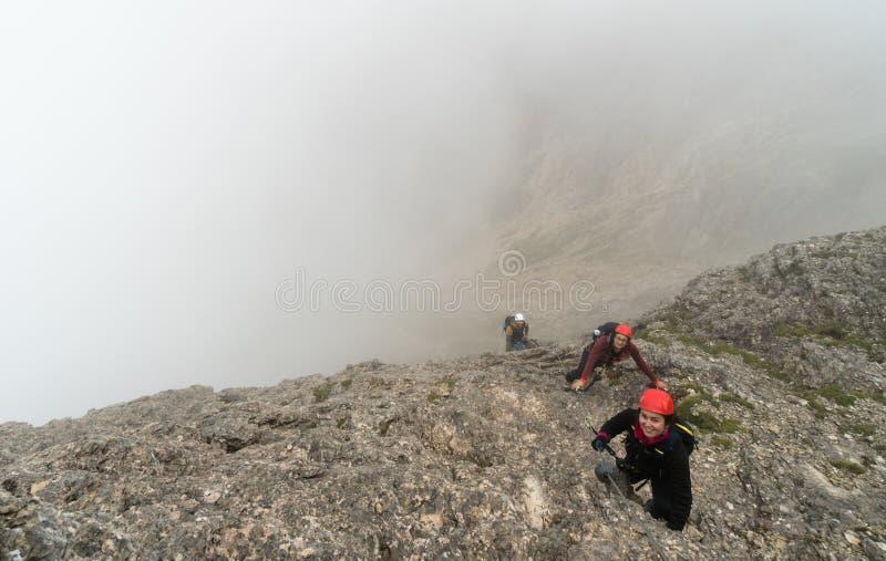 Τρεις νέοι ελκυστικοί θηλυκοί και αρσενικοί ορειβάτες βουνών στους δολομίτες της Ιταλίας στοκ φωτογραφία με δικαίωμα ελεύθερης χρήσης