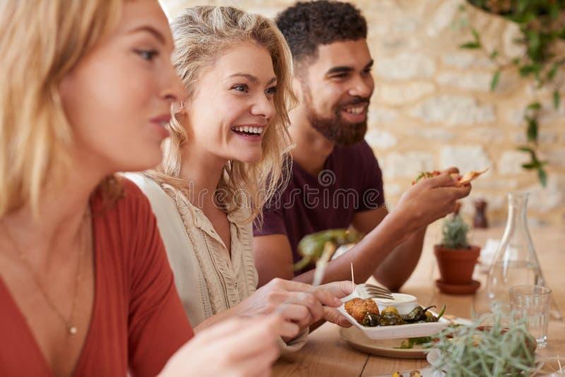 Τρεις νέοι ενήλικοι φίλοι που σε ένα εστιατόριο, κλείνουν επάνω στοκ φωτογραφία με δικαίωμα ελεύθερης χρήσης
