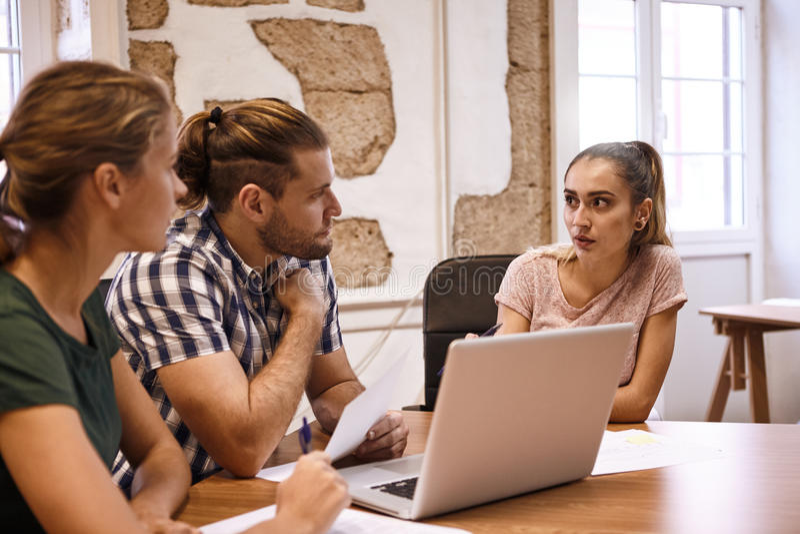 Τρεις νέοι επιχειρησιακοί επαγγελματίες στη συνεδρίαση στοκ φωτογραφία με δικαίωμα ελεύθερης χρήσης