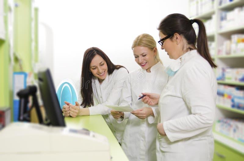 Τρεις νέοι θηλυκοί φαρμακοποιοί, που εργάζονται μαζί στην ομάδα στοκ εικόνα με δικαίωμα ελεύθερης χρήσης