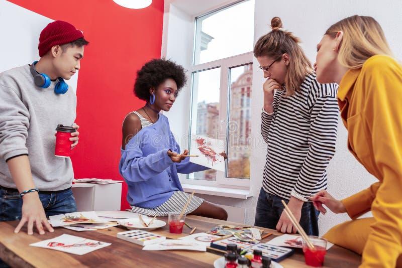Τρεις νέοι καλλιτέχνες που εξετάζουν την εργασία του δημιουργικού συναδέλφου τους στοκ φωτογραφίες