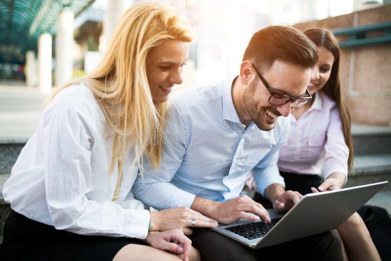 Τρεις νέοι χαμογελώντας συνάδελφοι που εργάζονται μαζί στο lap-top στοκ φωτογραφίες