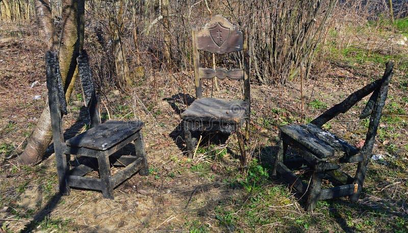 Τρεις παλιές καμένες και κατεστραμμένες ξύλινα καρέκλες στοκ φωτογραφίες