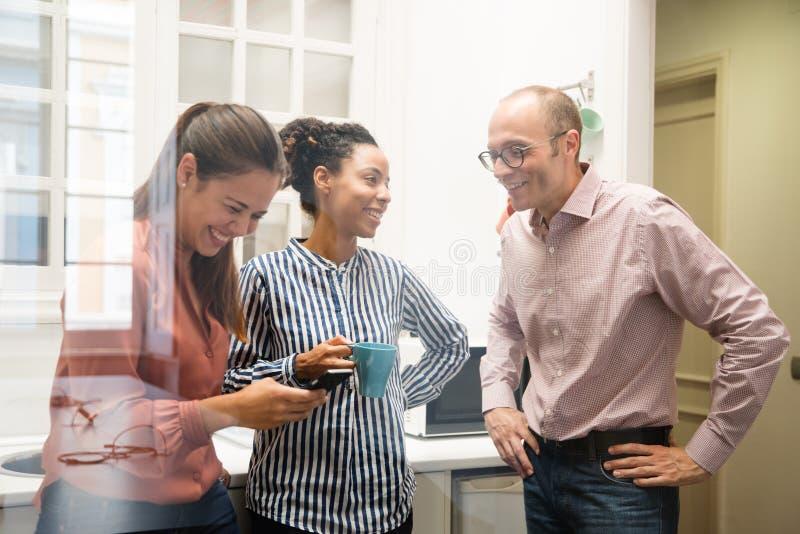 Τρεις συνάδελφοι εργασίας που γελούν σε μια κουζίνα στοκ εικόνες