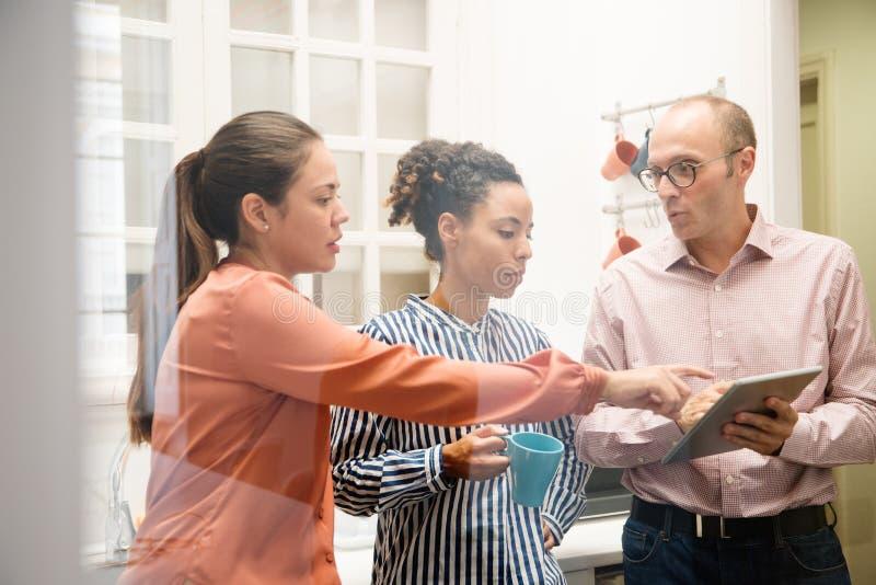 Τρεις συνάδελφοι που δείχνουν σε μια ταμπλέτα PC στοκ φωτογραφία με δικαίωμα ελεύθερης χρήσης