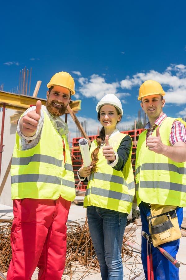 Τρεις συνάδελφοι σε μια ομάδα κατασκευής που παρουσιάζει αντίχειρες κατά τη διάρκεια της εργασίας στοκ εικόνες