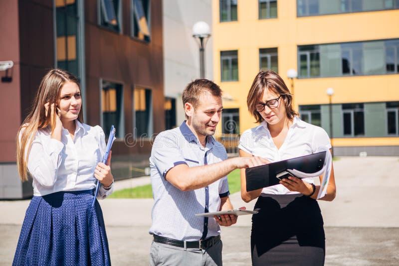 Τρεις συνάδελφοι που συζητούν την εργασία σε μια καινοτόμο πόλη στοκ εικόνα