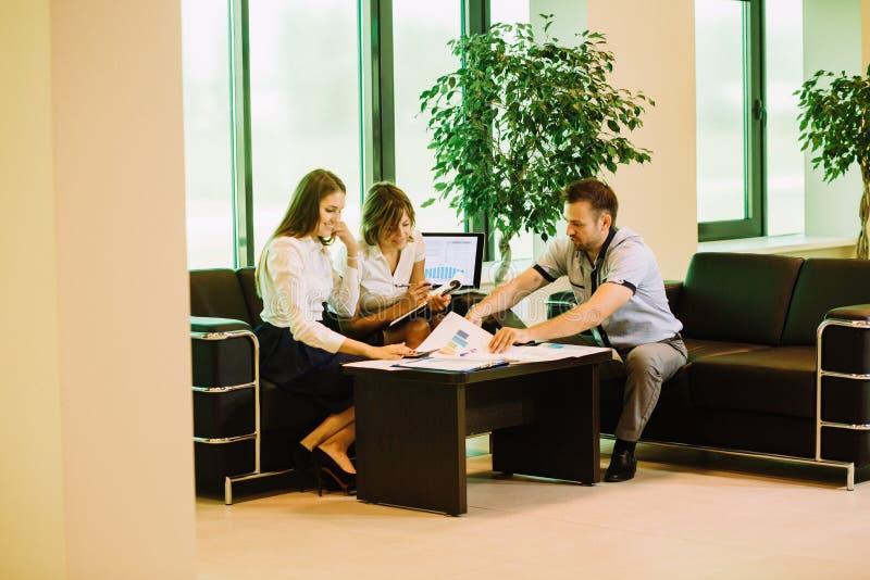 Τρεις συνάδελφοι που συζητούν τη μελλοντική εργασία επιχειρηματικών σχεδίων στοκ φωτογραφία