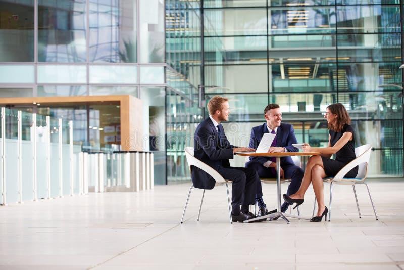 Τρεις συνάδελφοι σε μια συνεδρίαση στο φουαγιέ μιας μεγάλης επιχείρησης στοκ εικόνες