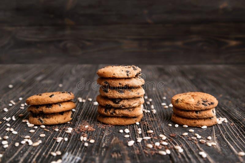 Τρεις σωροί των τραγανών μπισκότων τσιπ σοκολάτας σε έναν σκοτεινό ξύλινο πίνακα στοκ εικόνα