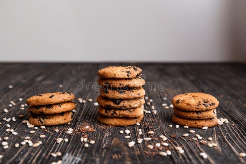 Τρεις σωροί των τραγανών μπισκότων τσιπ σοκολάτας σε έναν σκοτεινό ξύλινο πίνακα στοκ φωτογραφίες με δικαίωμα ελεύθερης χρήσης