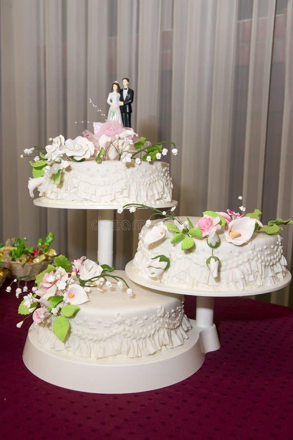 Τρεις-τοποθετημένο στη σειρά γαμήλιο κέικ στοκ εικόνες