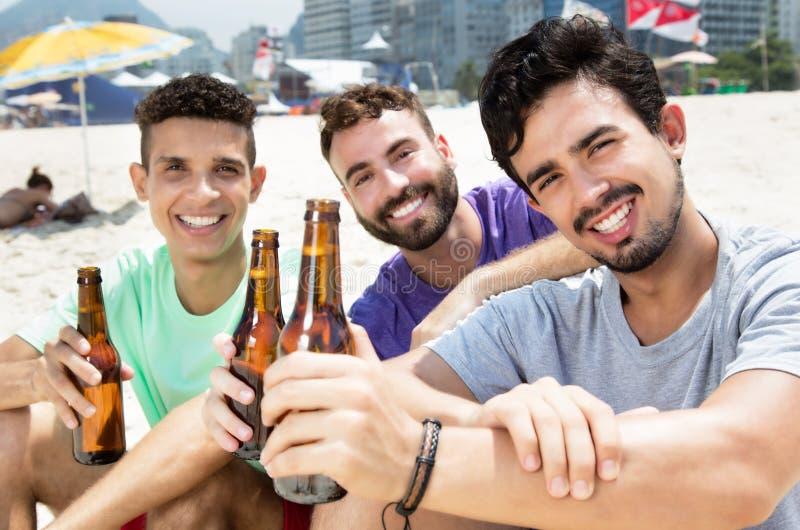 Τρεις τύποι που πίνουν την μπύρα στην παραλία στοκ φωτογραφία με δικαίωμα ελεύθερης χρήσης