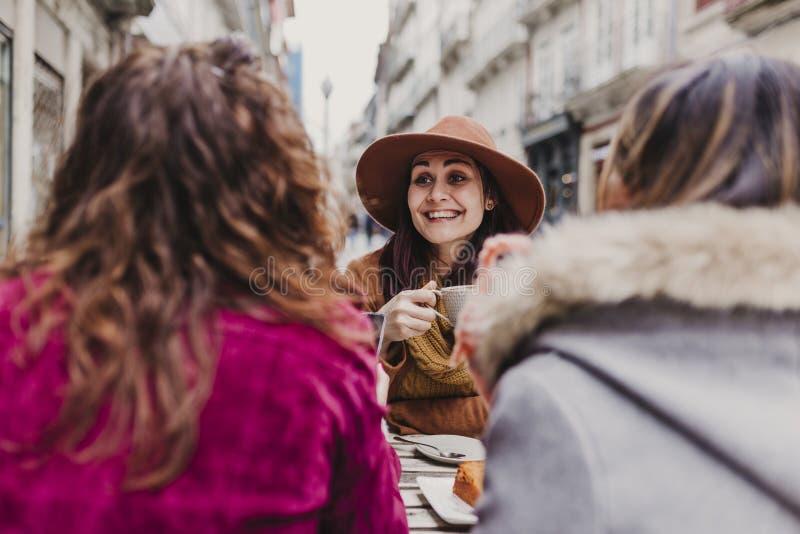 Τρεις φίλοι γυναικών που έχουν τον καφέ σε ένα πεζούλι στο Οπόρτο, Πορτογαλία Κατοχή μιας συνομιλίας διασκέδασης Τρόπος ζωής, του στοκ εικόνες