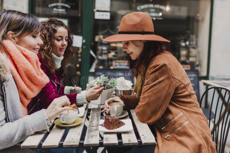 Τρεις φίλοι γυναικών που έχουν τον καφέ σε ένα πεζούλι στο Οπόρτο, Πορτογαλία Κατοχή μιας συνομιλίας διασκέδασης Τρόπος ζωής, του στοκ φωτογραφία με δικαίωμα ελεύθερης χρήσης