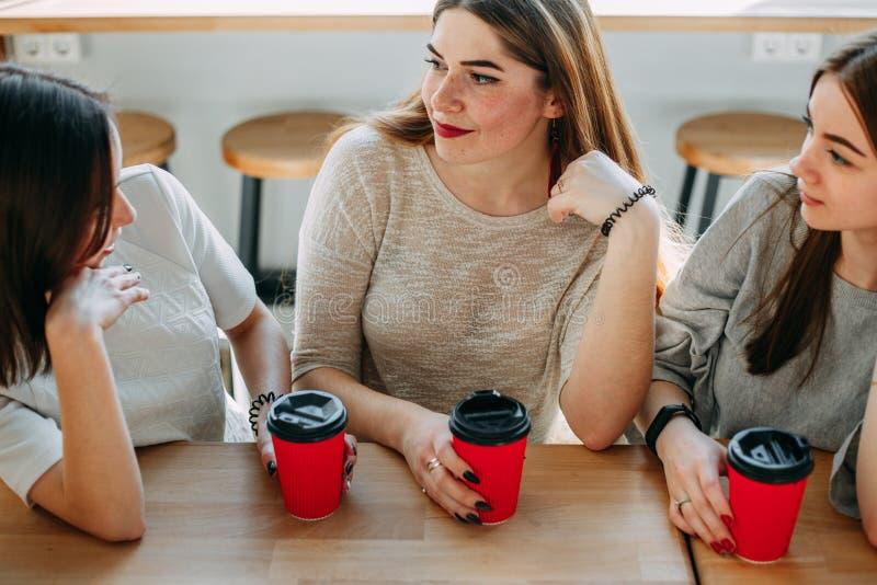 Τρεις φίλοι που έχουν έναν μεγάλο χρόνο στον καφέ στοκ φωτογραφία