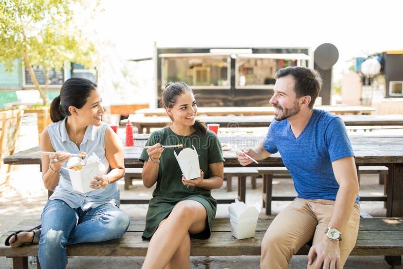Τρεις φίλοι που τρώνε τα ασιατικά τρόφιμα στοκ εικόνα